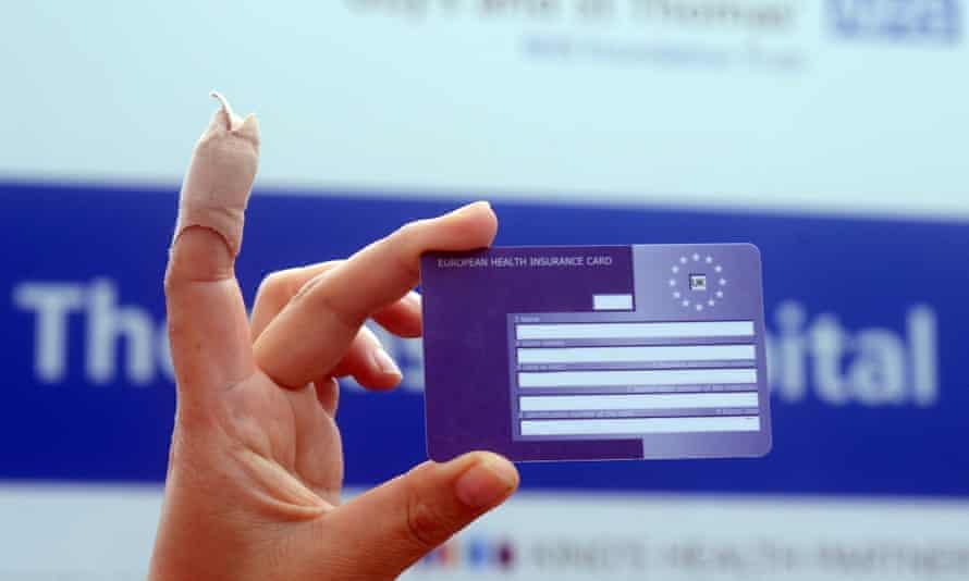A hand holding a European health insurance card