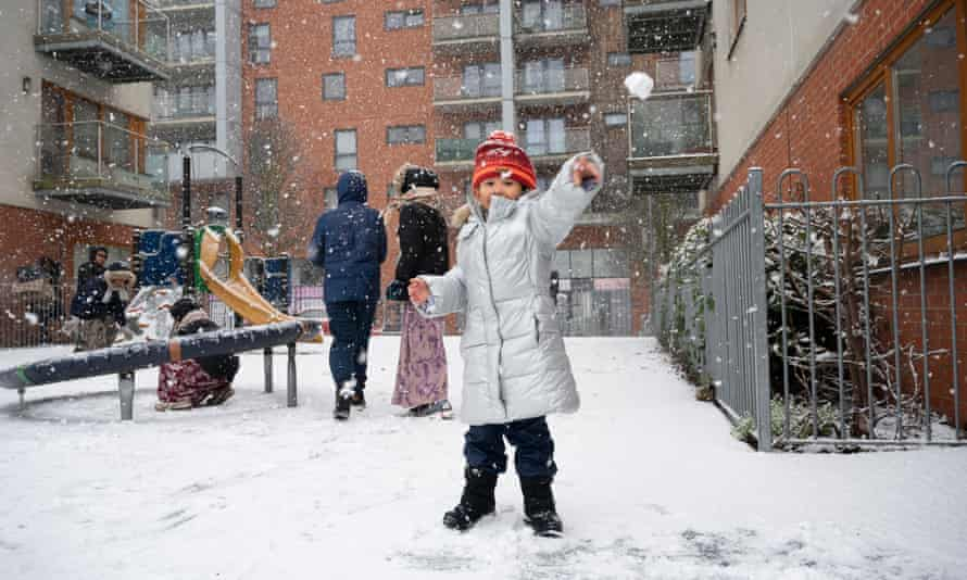 A girl throws a snowball in a playground in London.
