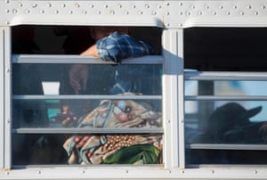A temporary agricultural worker looks out the window of a bus near the port of entry in San Luis, Arizona