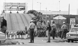 State troopers watch as marchers cross the Edmund Pettus Bridge as part of a civil rights march.