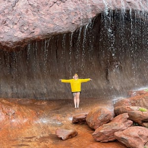 A woman poses under a mini-waterfall