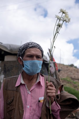 Don Pacho, 55, with a flower from his garden near his house at La Ville Nue in Bogotá on 29 May. He is an inhabitant of Altos de la Estancia. Authorities tore down 70% of his house.