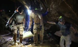 Rescuers carry the boys out of the Tham Luang cave complex.