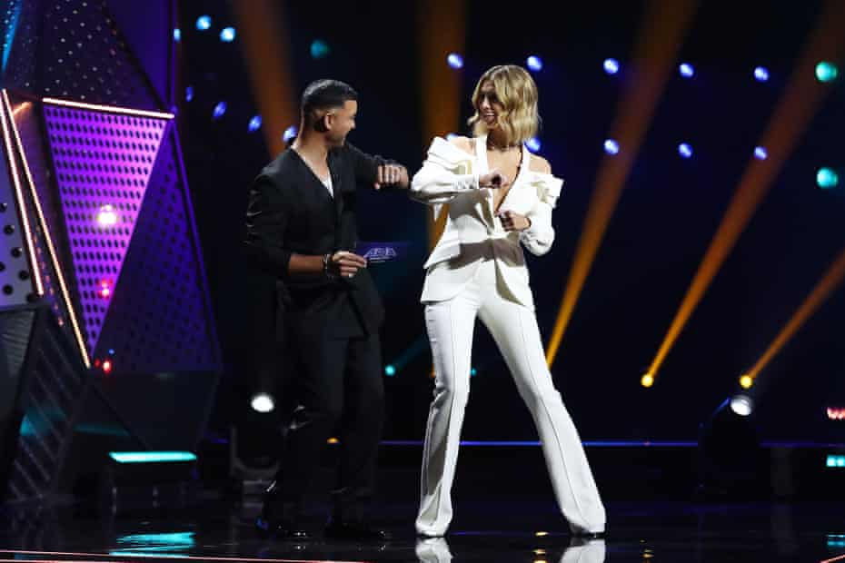 Guy Sebastian and Delta Goodrem elbow bump on stage at the Star Casino.