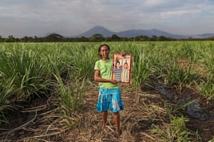 Sugarcane worker Maria Esther Ulloa Orozco holds up a picture of