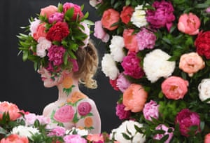 London, UK A model poses for photographers next to a floral display during the press day for the RHS Chelsea Flower Show. The RHS Chelsea Flower Show is held for five days by the Royal Horticultural Society in the grounds of the Royal Hospital Chelsea.