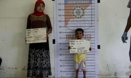 A Rohingya woman and a child from Burma are photographed during identification procedures at a newly set up confinement area in Aceh province in Indonesia after hundreds of migrants from Burma and Bangladesh were rescued by Indonesian fishermen off the waters of the province on 20 May.