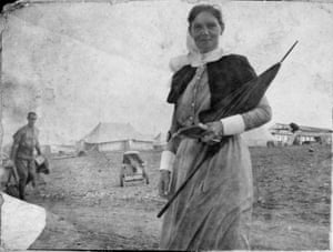 Holding a parasol and notebook, matron (Margaret) Grace Wilson does a round on Lemnos, an island in Greece, 1915.