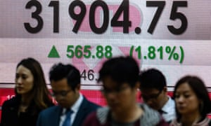 people in Hong Kong walk past the latest Hang Seng index figures