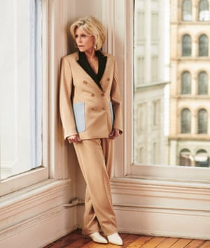 Jane Fonda wearing a camel suit standing in the corner of a room by two big windows