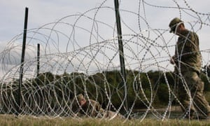 Soldiers work on installing concertina wire at the US-Mexico border.
