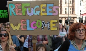 A child holds a placard saying 'refugees welcome' during a solidarity march in London.