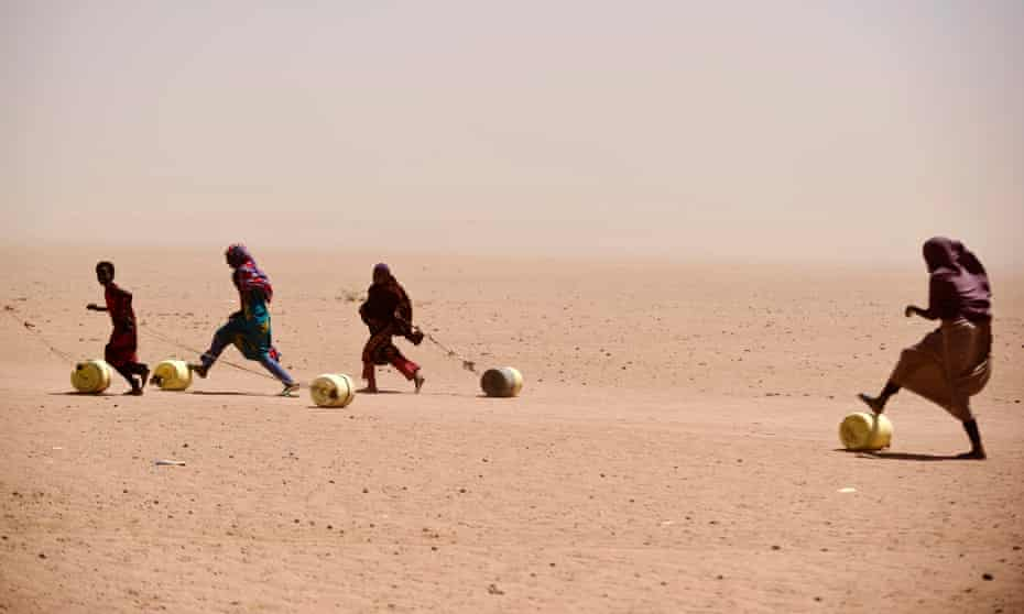 People roll water containers in drought-hit Wajir, Kenya.