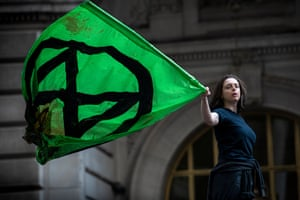 Standing on the Charging Bull near Wall Street in lower Manhattan, a member of the Extinction Rebellion waves their flag covered in fake blood.