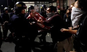 A masked demonstrator scuffles with police officers during a second night of protests in Oakland, California
