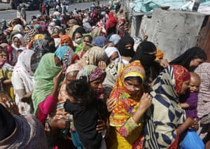 People wait to receive food aid in Lahore, Pakistan