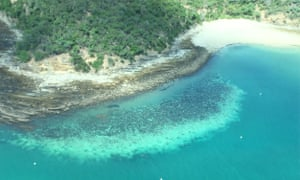aerial shot of bleached coral off a reef island
