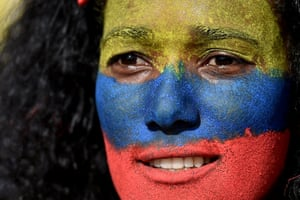 A woman with her face painted in the colours of the Colombian flag takes part in a protest in Cali
