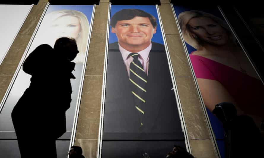 People pass by a promo of Fox News host Tucker Carlson on the News Corporation building in New York.