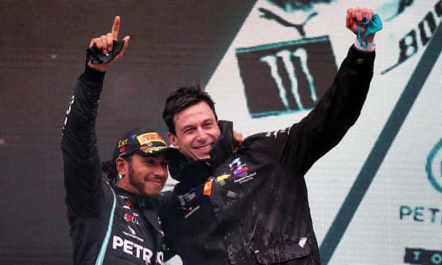 Toto Wolff celebrates on the podium with Lewis Hamilton.