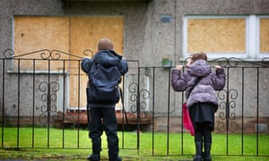 Children in front of a boarded-up flat