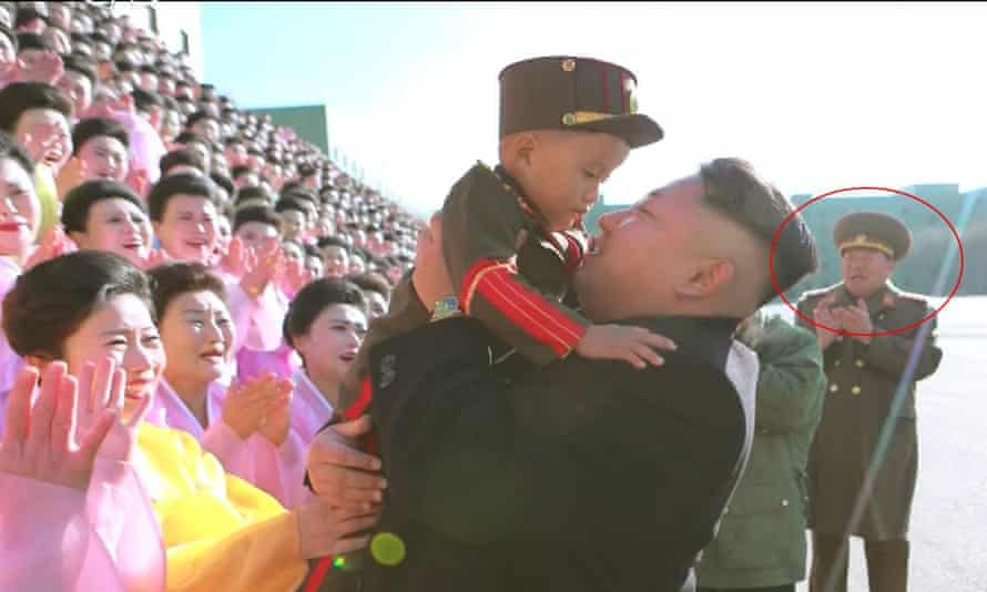 Dead or alive: Kim Jong-un holding a baby with defence minister Hyon Yong-chol circled in the background, who has been reported executed.