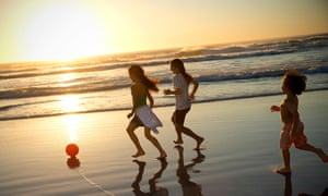 Three children playing with ball on the beach at sunset