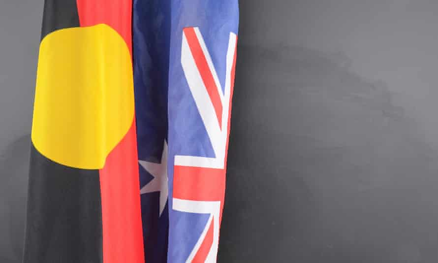 An Aboriginal flag hangs next to an Australian flag in front of a blackboard
