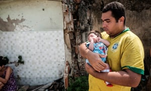 A resident of Rio's Vila Autódromo community stands outside his home with his baby daughter