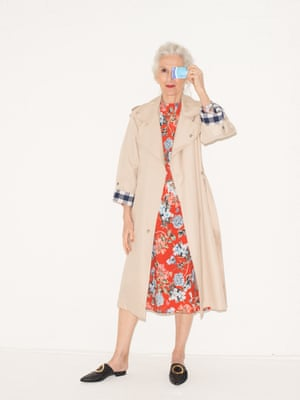 beige trench coat House of Sunny, red dress with pink green grey blue floral design H&M flat slip on black shoes with gold hoops on front Neous from Net A Porter