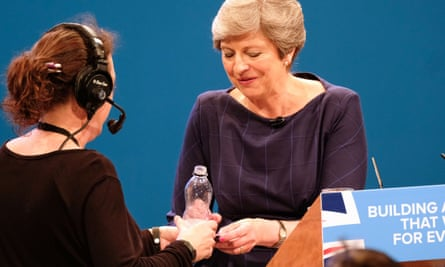 An assistant brings Theresa May bottled water  during her speech on Wednesday.