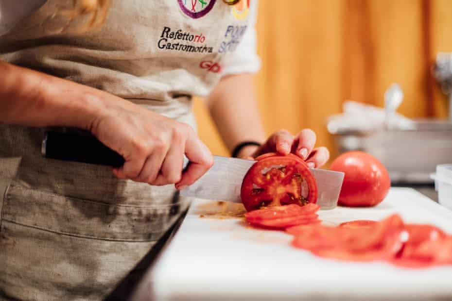 chopping tomato in Refettorio Gastromotiva