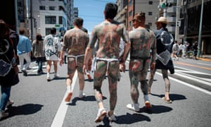 Participants with traditional Japanese tattoos, related to the Yakuza, walk through the Asakusa district during the annual Sanja Matsuri festival in Tokyo