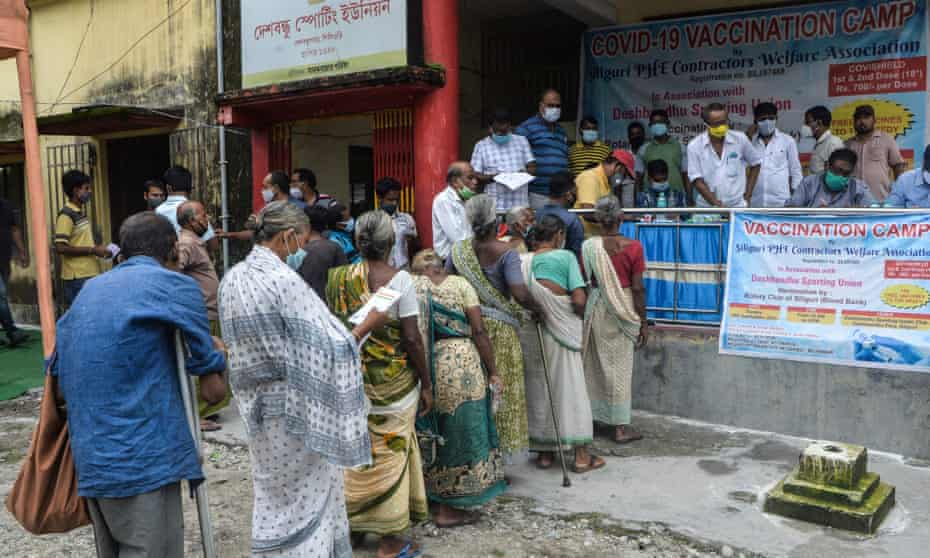 People stand in a queue as they wait to receive a dose of Covid vaccine in Siliguri, West Bengal, India.