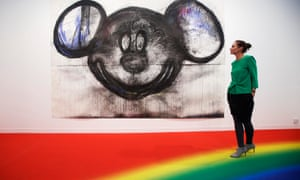 A visitor poses with artist Joyce Pensato's Mickey for Micky at the 2014 Frieze Fair in London.