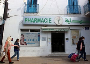 People wearing masks walk past a pharmacy in Tunis, where a curfew will be imposed in an effort to slow a surge in coronavirus cases.