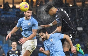 Aston Villa's Tyrone Mings beats Manchester City's Ruben Dias and Ilkay Gundogan in the air.