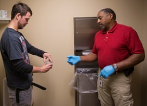 "Charles ""Bubba"" Rouse handing a drug test cup filled with his urine to Drug Court Coordinator, Chris Brown"