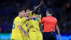 Porto's Danilo Pereira and his team-mates surround referee Cuneyt Cakir at half-time.