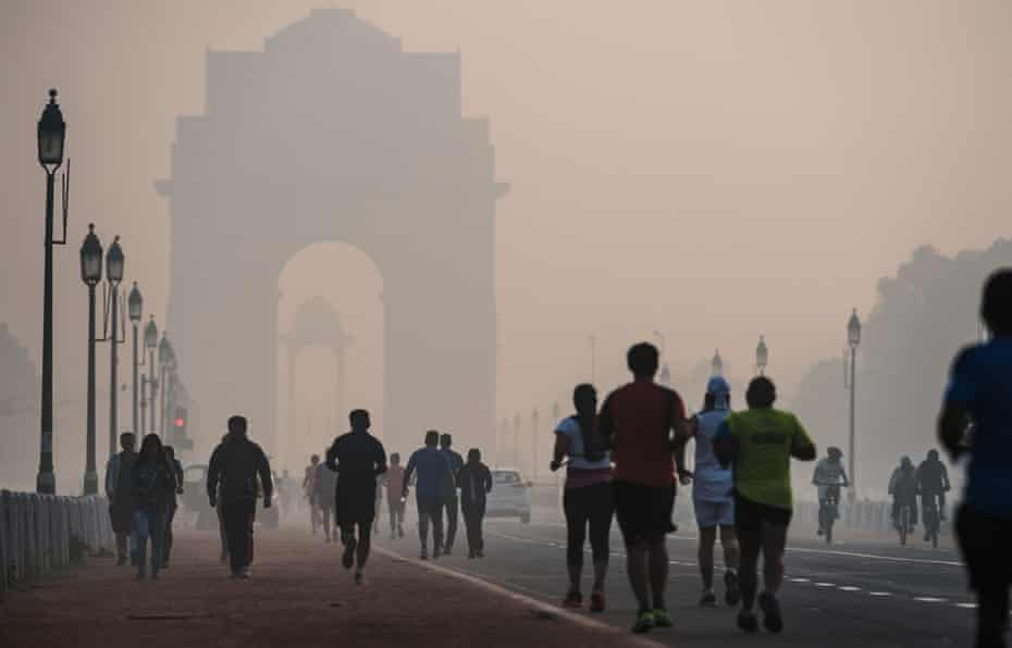 Joggers and walkers on a smoggy morning near the India Gate monument in New Delhi.