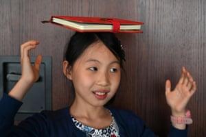 Danielle Liu balances a book on her head