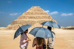Cairo, EgyptVisitors with umbrellas shelter from the sun while viewing the step pyramid of Pharaoh Djoser of the third dynasty at the Saqqara Necropolis.