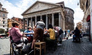 People have lunch outside a restaurant near the Pantheon, in the centre of Rome