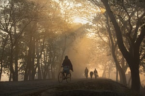 A man rides a bicycle on a foggy morning in Guwahati, India