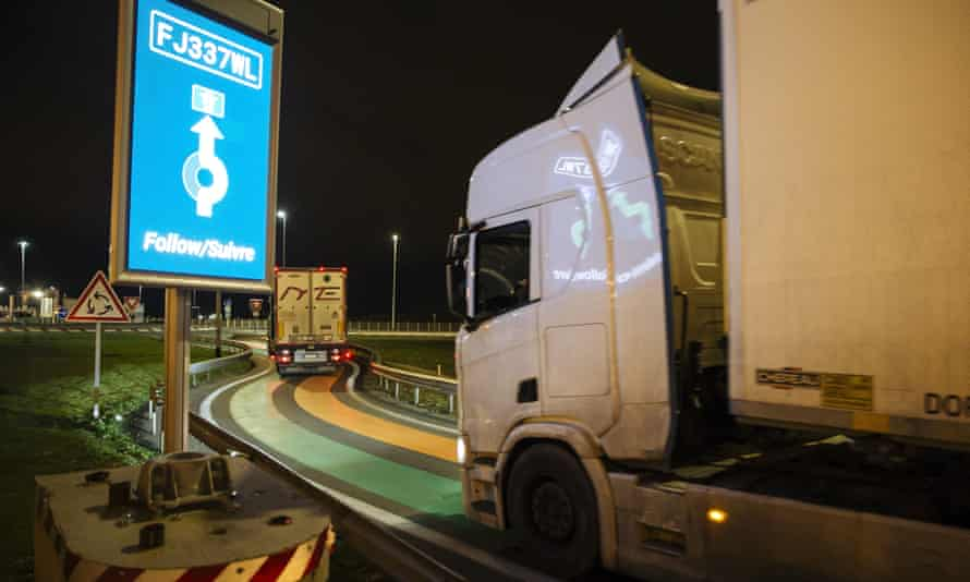 A truck from Britain drives over green and orange lines on the road that is part of the new 'smart border' customs infrastructure to enter France at the Eurotunnel terminal