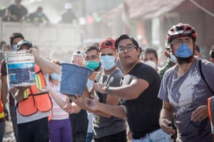 Rescuers form a human chain as they look to clear rubble and bring supplies to those further up the chain.