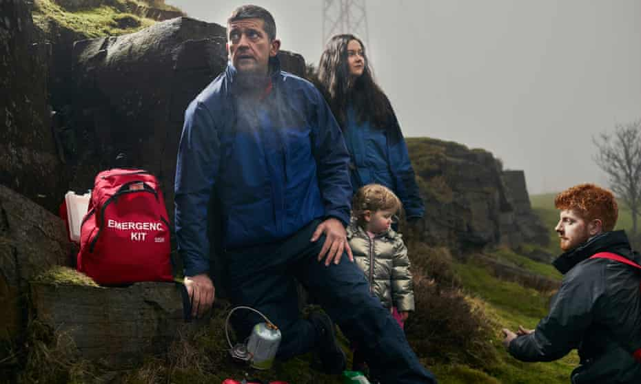 Shaun Leonard and family, dressed in thick coats and with a bag labelled 'emergency kit', standing around a rocky outcrop in remote moorland