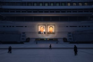 People walk past illuminated portraits of late North Korean leaders Kim Il-sung, left, and Kim Jong-Il