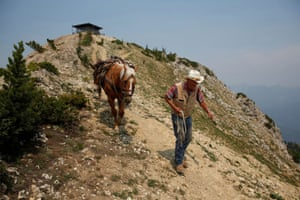 Norman Kamrud, 78, leads his horse Blueberry and pack mule Jumper down the rocky path from the Patrol Mountain fire lookout after completing radio maintenance work.