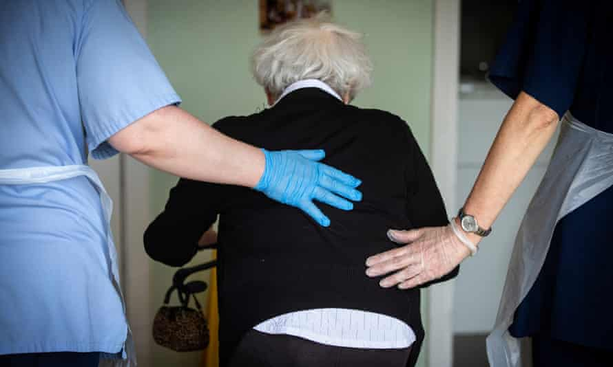 Care workers help an older person to walk in a care home